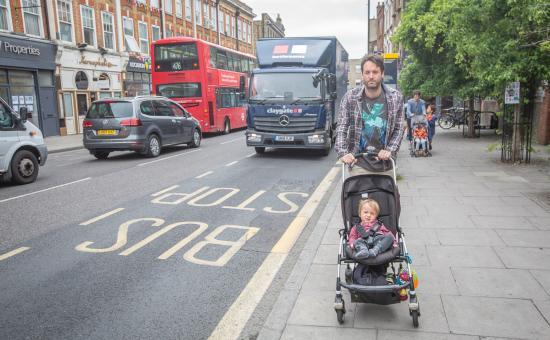 photo of man walking with buggy beside traffic